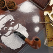 Santa made of snow spray smoking pipe on wooden desk with items — Stock Photo #36706979