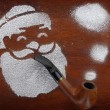 Santa made of snow spray smoking pipe on wooden background — Stock Photo