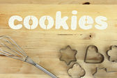 """Stencil word """"cookies"""" made with flour on wooden table — Stock Photo"""