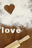 "Stencil word ""love"" made with flour on wooden table — Stock Photo"