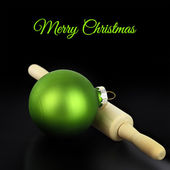Christmas ball with rolling pin on black background — Stock Photo