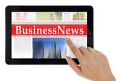 Hand scrolling digital news on tablet computer — Stock Photo