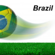 Soccer ball with Brazil flag in motion with grass isolated — Zdjęcie stockowe