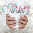 Female hands holding white bucket with candy canes — Stock Photo #38967507