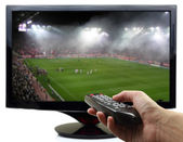 Tv screen with football match and hand with remote control — Stock Photo