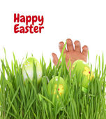 Hand reaching for Easter egg on green grass — Stock Photo