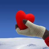Woman hand holding a red heart on a snowy background — Stock Photo