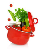 Colorful vegetables coming of a red cooking pot — Stock Photo
