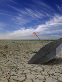 Dry deserted landscape with open black umbrella. — Stock Photo
