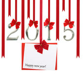 2015 number and Christmas greeting card hanging on red ribbons — Stock Photo