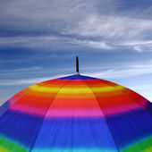 Rainbow colored umbrella top with blue sky above it — Stock Photo