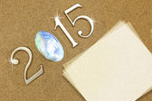 Year 2015 numbers with blank paper card on the sand — Stock Photo