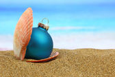 Hristmas ball in a sea shell on the beach — Стоковое фото