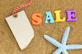 Blank tag, colorful sale text and starfish on sand — Stock Photo