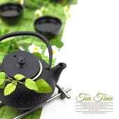Teapot with fresh green herbs, flowers, cups and copy-space — Stockfoto
