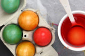 Colored Easter eggs and liquid color dyes — Stock Photo