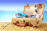Full open suitcase on tropical beach background — Stock Photo
