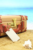 Closed suitcase with empty tag on tropical beach background — Stok fotoğraf