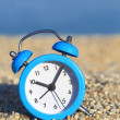 Vacation time. Alarm clock on the beach — Stock Photo