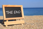"Blackboard with ""The end"" text on the beach — Stock Photo"