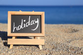 Blackboard with holiday text on the beach  — Stock Photo