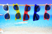 Colorful Sunglasses hanging on a rope in front of the sea — Stockfoto