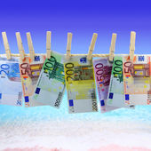 Banknotes hanging on clothesline in front of the beach — Stock Photo