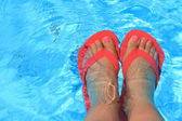 Female feet with flip flops in water — Stockfoto