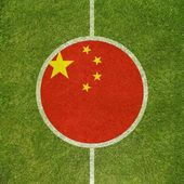 Football field center closeup with Chinese flag in circle  — Zdjęcie stockowe