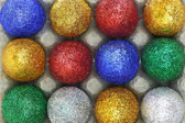 Colorful glitter eggs in carton egg packaging closeup — Stock Photo