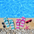 Flip flops, glasses and starfish by the poolside — Stock Photo #50360025