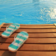 Flip flops on wooden sunbed and water — Stock Photo #50360147