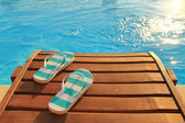 Flip flops on wooden sunbed and water — Stock Photo