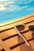 Sunglasses on wooden planks and water on sunset  — Stock Photo