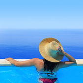 Woman in hat overlooking the seascape from the poolside  — Foto Stock