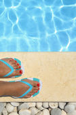 Female feet with flip flops by the pool  — Foto Stock
