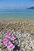 Flip flops on pebbled beach Vassiliki Lefkada  — Stock Photo