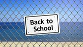 Beach enclosed by fence with sign Back to School  — Stock Photo