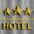 Five golden stars and word Hotel on grey wood — Stockfoto #51770053