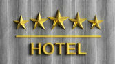 Five golden stars and word Hotel on grey wood  — Stock Photo