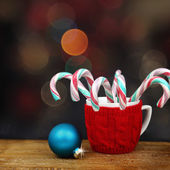 Christmas ball and candy canes in front of sparkle lights — Stock Photo