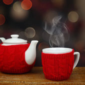 Teapot and cup in front of sparkle lights background — Stock Photo