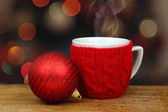 Christmas ball and hot drink in a cup in front of sparkle lights — Stock Photo