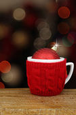 Christmas ball in a cup in front of sparkles night background — Stock Photo