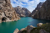 Kelsu mountain lake with turquoise colour of water and wonderful rocks and blue sky with clouds. — Stock Photo