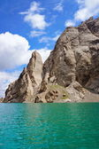 Amazing Kelsu mountain lake between the stunned rocks and blue sky with clouds — Stock Photo