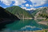 Lago encantador entre altas montanhas pitorescas e uma nuvem no céu azul — Foto Stock