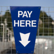 Blue Pay Here Sign - Stock Photo
