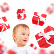 Little boy smiling and many gift boxes falling around him. Merry — Stock Photo