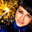 Portrait of young attractive celebrating woman holding sparkles — Stock Photo #12718764